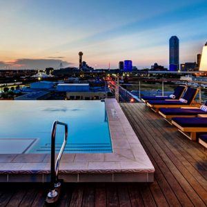Rooftop pool deck overlooking a sunset at CANVAS Hotel in Dallas, TX