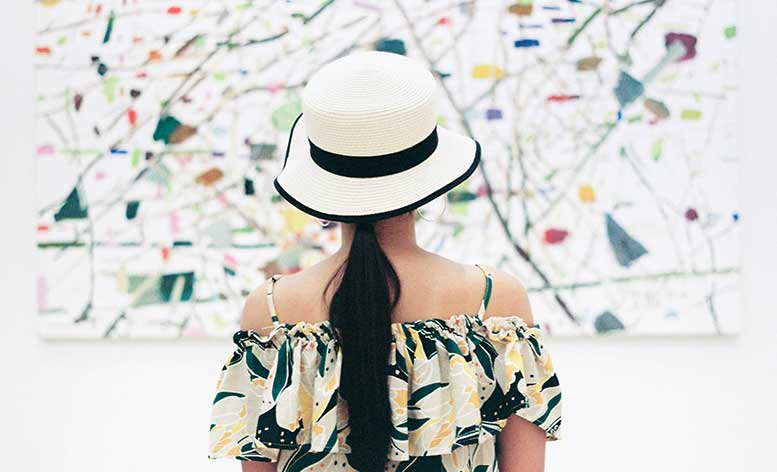 Lady wearing a hat looking at an artwork piece on a wall at CANVAS Hotel.